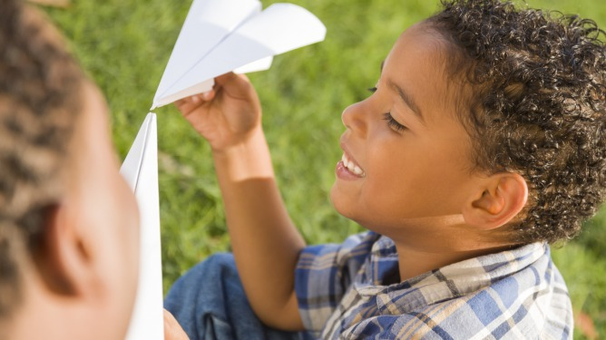 2 young boys playing with a paper airplane