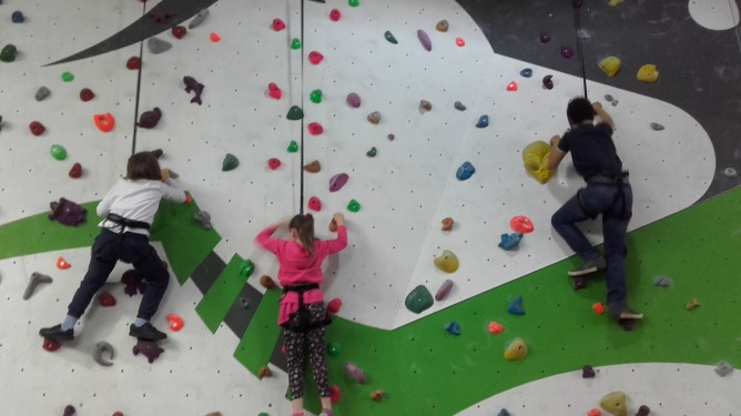 young adopted children climbing rock play wall