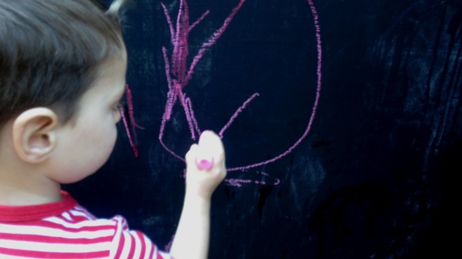 Young boy drawing on a chalk board